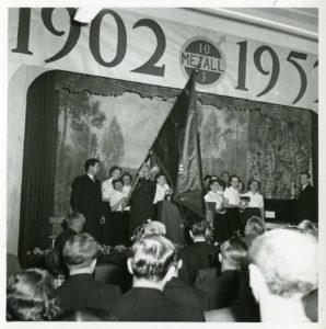 """En grupp kvinnor på en scen. En av dem håller i en fana. Ovanför scenenen texten """"1902-1952""""."""