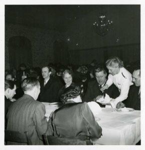 En kvinna i vit blus serverar människor som sitter vid långbord med vita dukar.