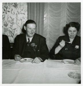 Närbild på man och kvinna som sitter och äter vid ett bord med vit duk.