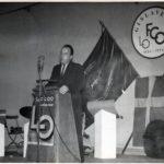 En man står vid en talarstol på en scen med en mikrofon. I bakgrunden En fackfana och en svensk flagga.