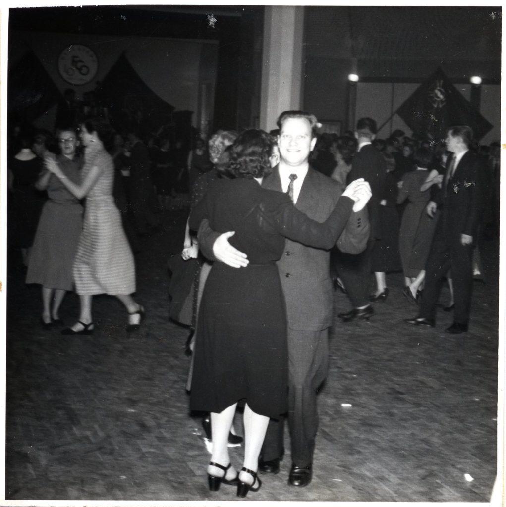 Några dansande par på ett dansgolv. I bakgrunden på väggarna syns fanor.