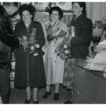 Tre kvinnor förefaller bli intervjuade samt få blommor och andra saker i en butik från en äldre man.