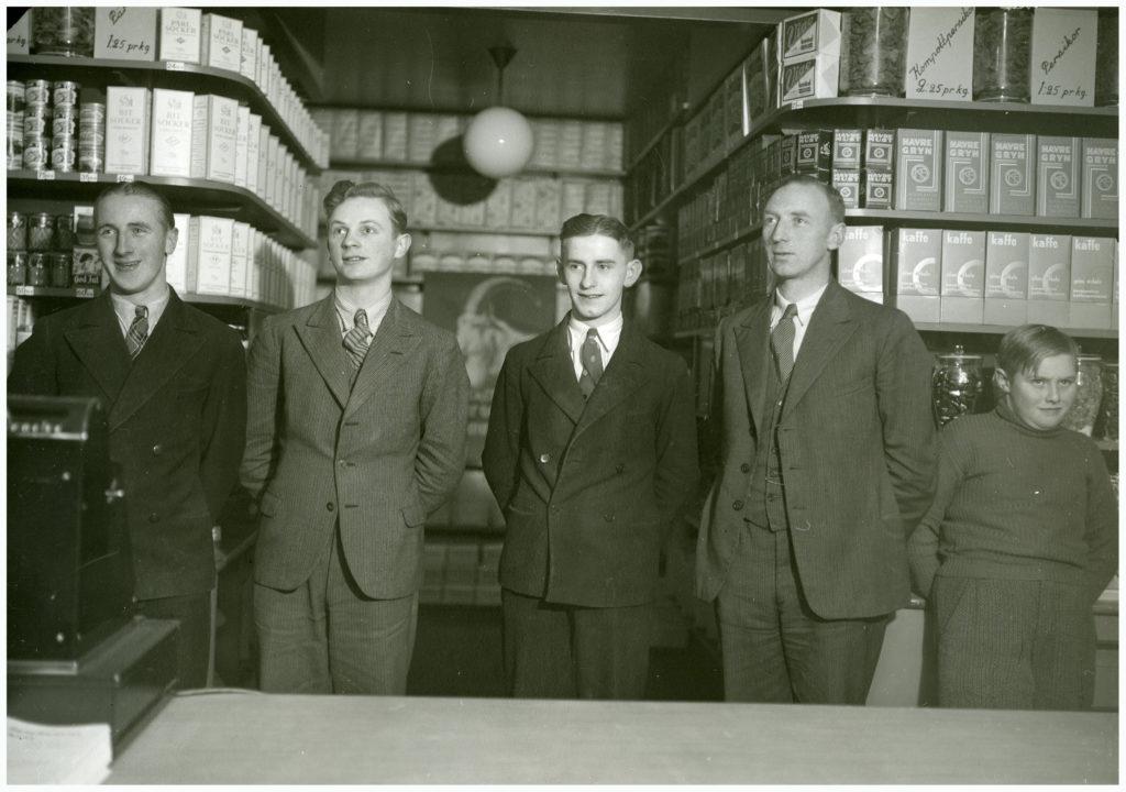 Fyra unga män och en pojke bakom en köpdisk.