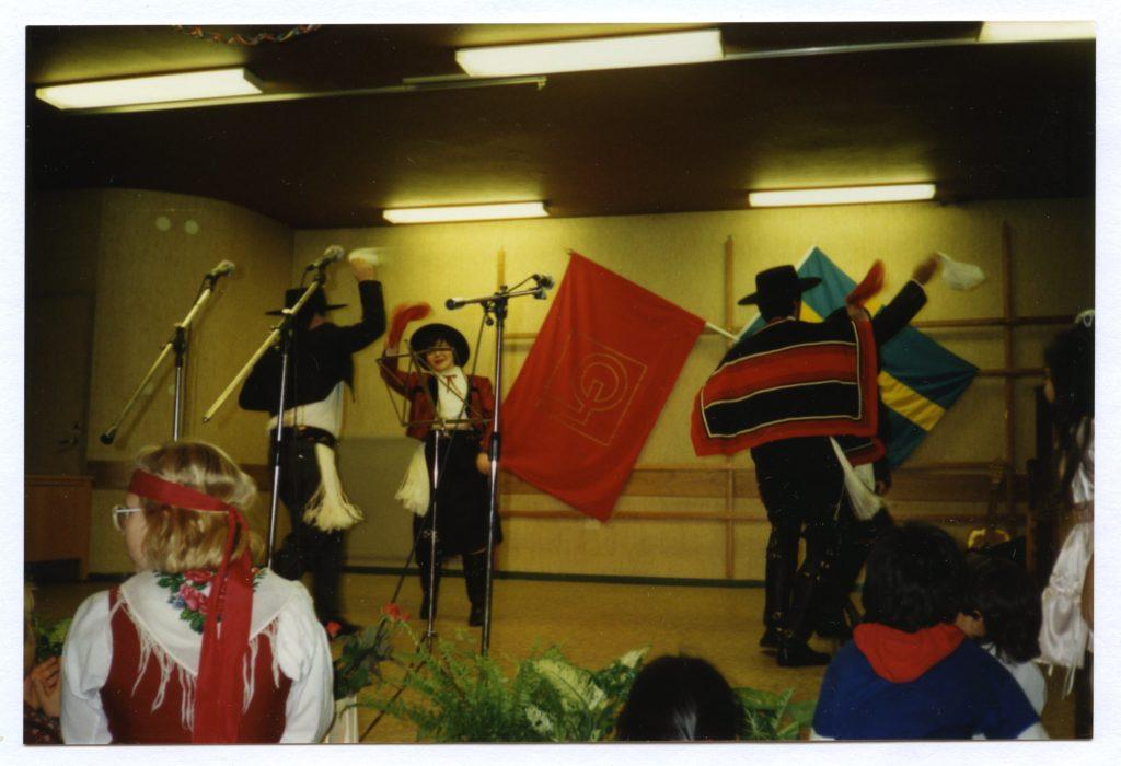Några män och kvinnor dansar och spelar på en scen. I bakgrunden på väggen hänger en svensk flagga och en LO-fana. Artisternas kläder för tankarna till spansk folkmusik.