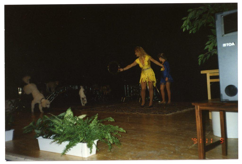 En kvinna i gul klänning uppträder på en scen med dresserade hundar som gör tricks.