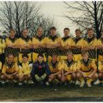 17 fotbollsspelare i svargula matchställ uppställda på gräsmatta. I bakgrunden skymtar några träd utan löv.