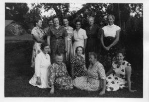 Fem kvinnor sitter på en gräsmatta, bakom dem står åtta kvinnor. I bakgrunden skymtar något som skulle kunna vara äppelträd.