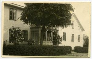 Foto av veranda med mycket snickarglädje. Två personer befinner sig på verandan.
