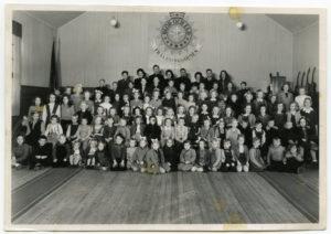 Gruppbild på ett hundratal barn och ungdomar i en stor sal.