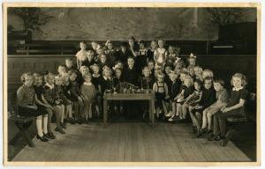 Gruppbild på barn samlade i en stor sal kring ett bord med träfigurer på.