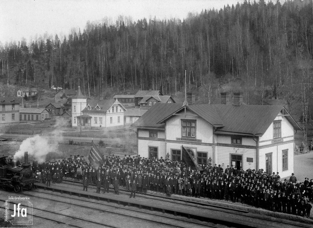 Svartvitt foto. Vy över folksamling på perrong vid en tågstation. Till vänster i bilden skymtar ett lok med en vit rökplym ur skorsstenen.