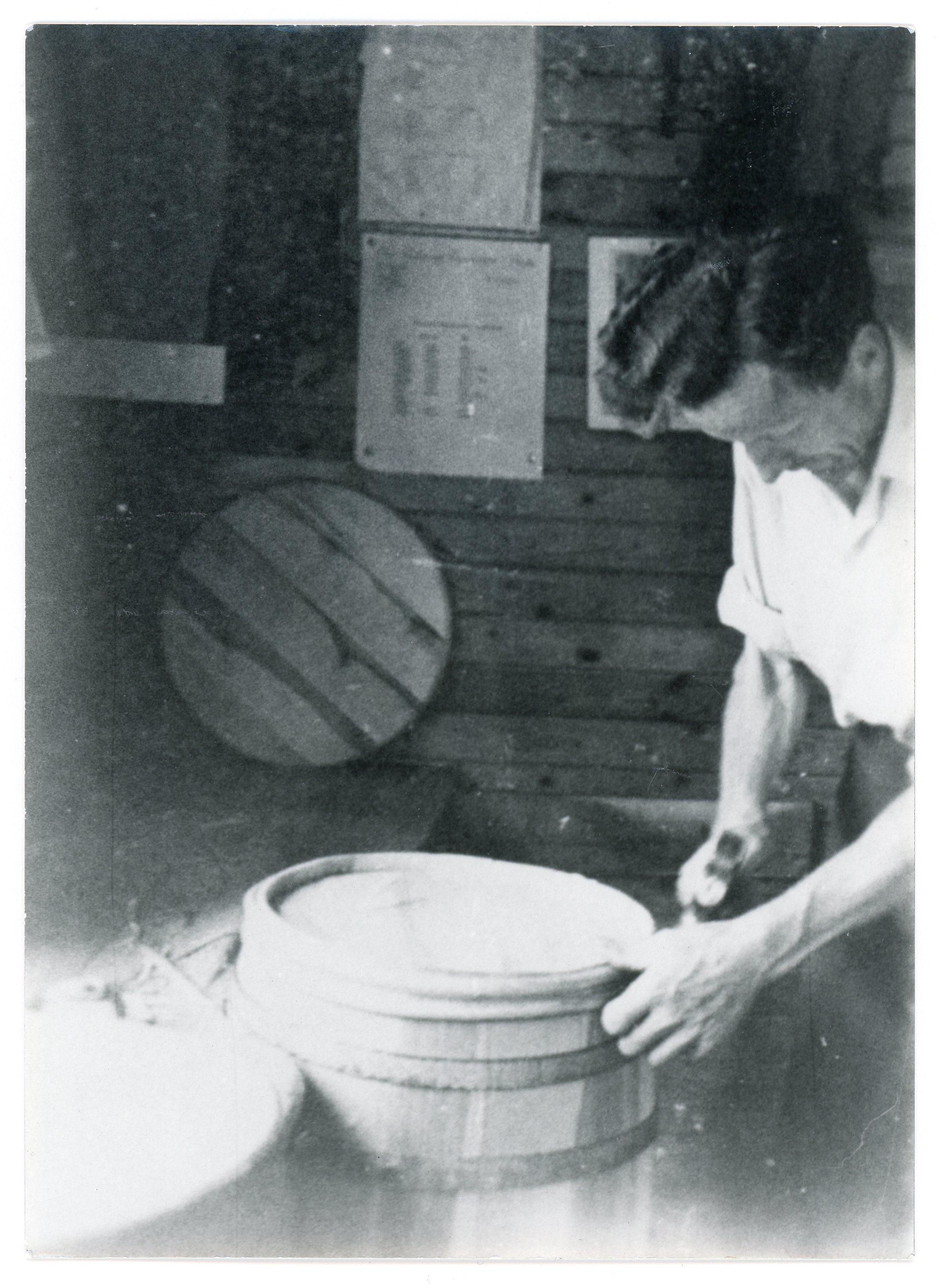 En man i vit skjorta står böjd över en tunna i en snickeriverkstad. Han binder tunnan med band. Hans underarmar är seniga och ådriga. Väggen bakom honom består av liggande brädor. På väggen hänger ett runt trälock.