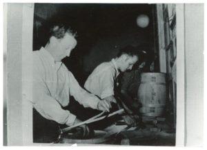 Två män arbetar med att binda tunnor vid en bänk.