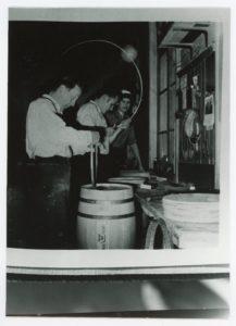 Tre män arbetar med att binda tunnar i en snickeriverkstad.