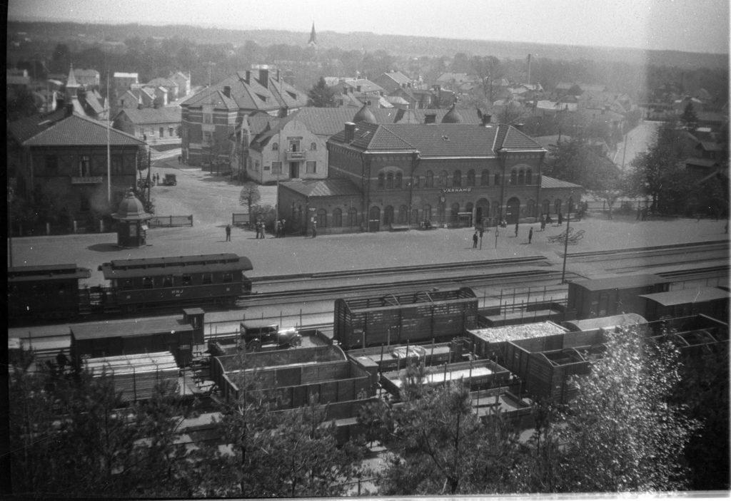 """Svartvitt fotografi tagen från en höjd. I förgrunden växlighet, därefter järnvägsspår och därefter en perrong med en tegelbyggnad på vilken en skylt med texten """"Värnamo"""" sitter. I bakgrunden bebyggelse och i fjärran skog."""