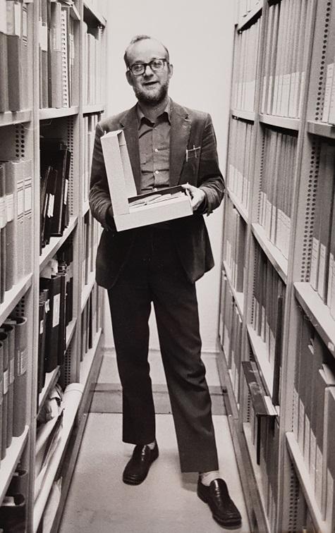 En man i glasögon står i en gång omgärdad av hyllor med arkivboxar och pärmar. I handen håller han en öppnad arkivbox.