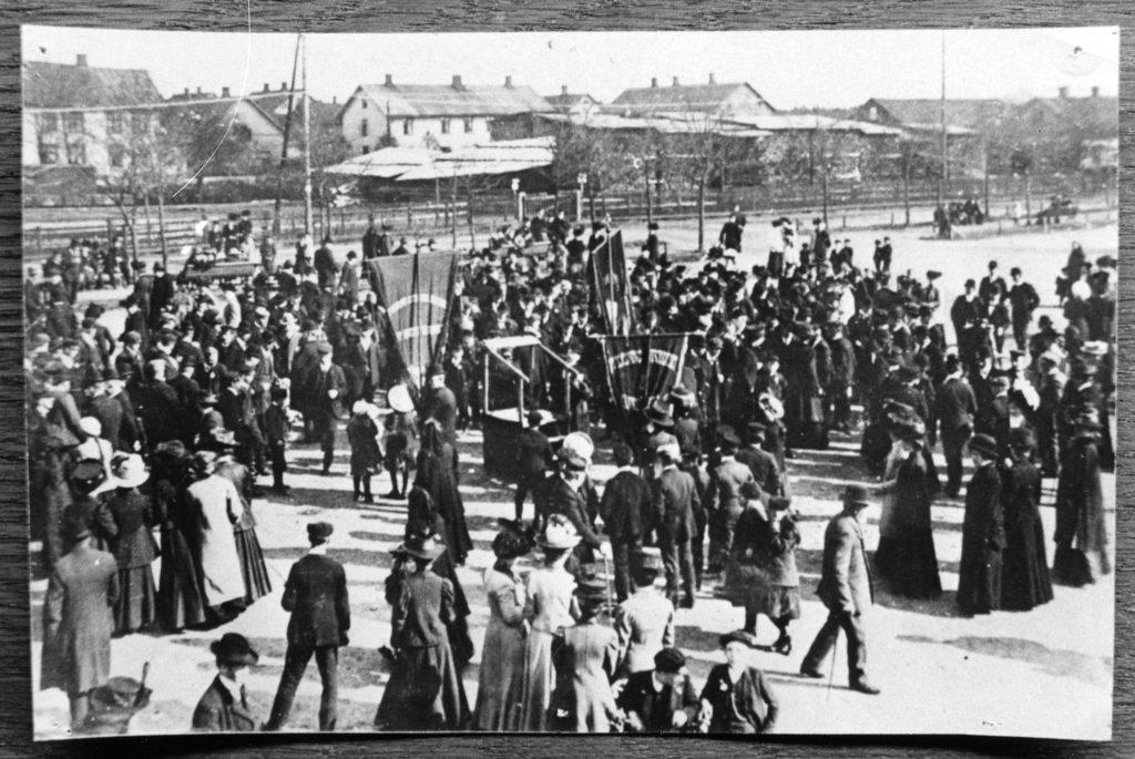 Något suddigt svartvitt foto över folksamling på ett torg. I mitten finns ett en talarstol och ett antal fanor. I bakgrunden skymtar bebyggelse.
