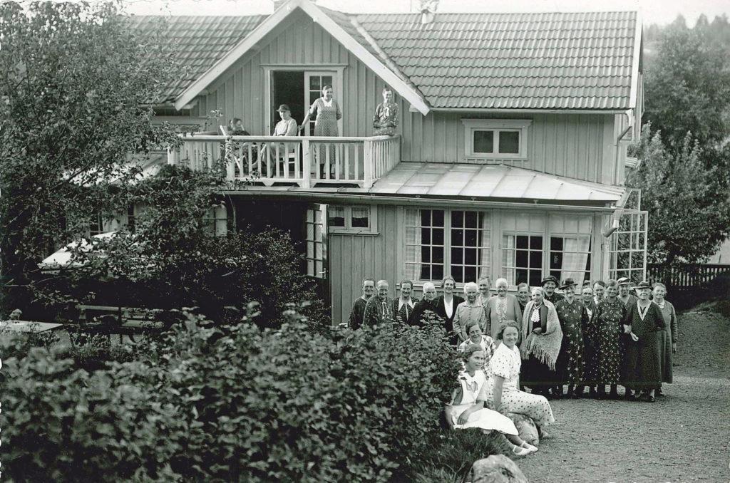 """En grupp kvinnor på semesterhemmet """"Mors Vila"""" vid Vista kulle (Bergsäter, Skärstad). Byggnaden är omgiven av buskar och träd. Framför verandan poserar en stor grupp kvinnor, även på balkongen ses några av gästerna."""