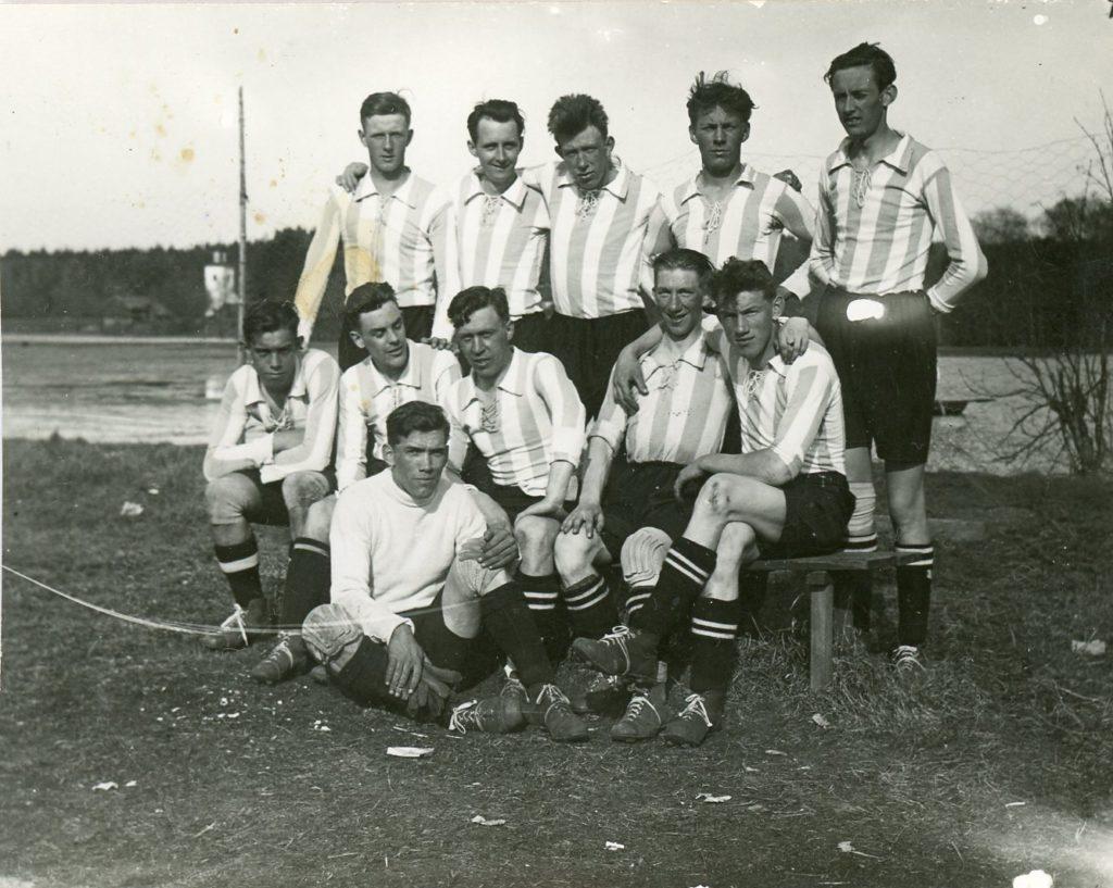 Svartvitt fotografi på fotbollslag i randiga tröjor. Fem stycken står och sex stycken sitter framför.