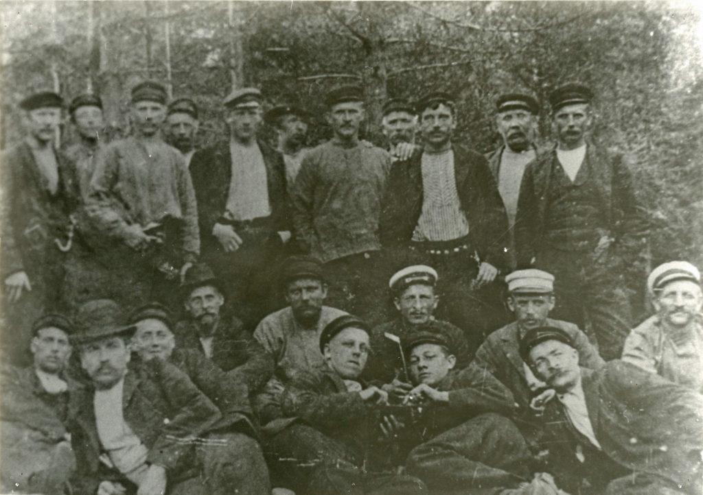 Svartvitt foto på ett tjugotal män i olika åldrar uppställda för foto. I bakgrunden skog.