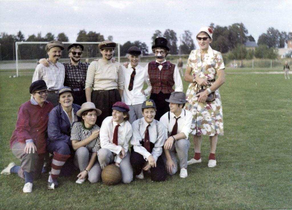 Elva kvinnor utklädda i hattar, slipsar, lösskägg. En man i klänning, hatt och solglasögon. Uppställda på en fotbollsplan.