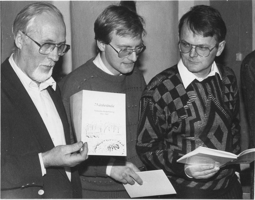 Tre män håller upp jubileumsskrift.