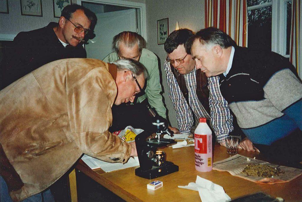 Fem män böjda över ett bord på vilket ett mikroskop står.