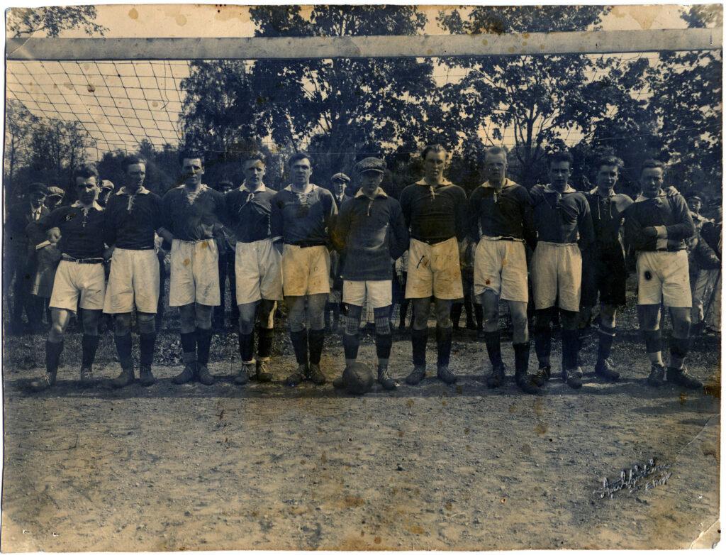 11 stycken män i fotbollskläder poserar framför ett fotbollsmål. I bakgrunden, bakom nätet, skymtas några nyfikna åskådare.
