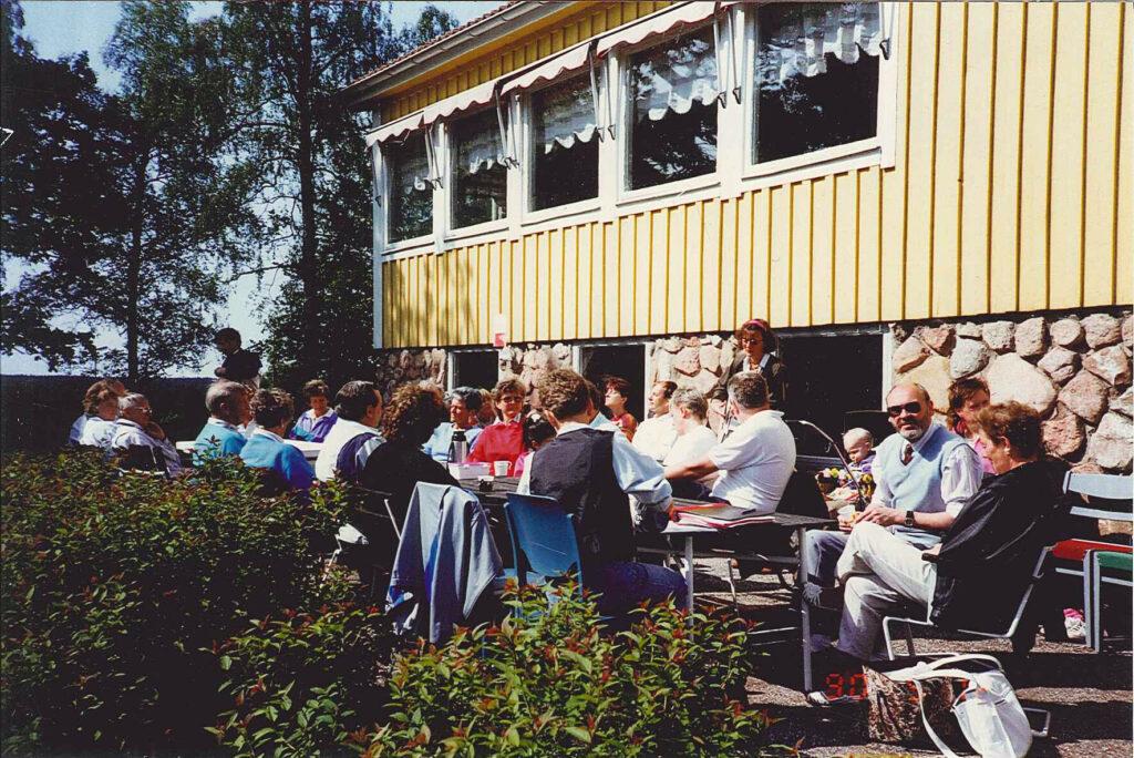 Bild på människor som sitter vid bord och fikar.