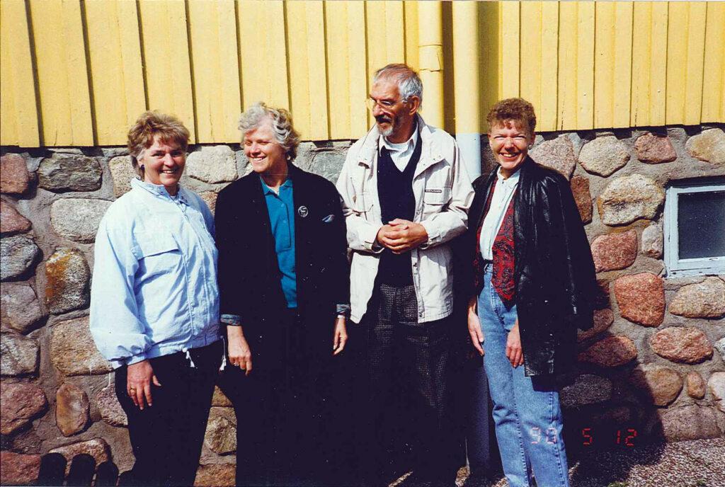 Fyra personer uppställda för foto framför en gul trävägg