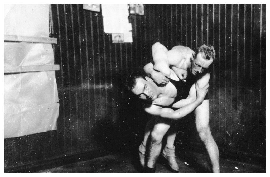 Två stycken manliga brottare poserar för bild. Den ena brottaren har kopplat grepp om den andre.