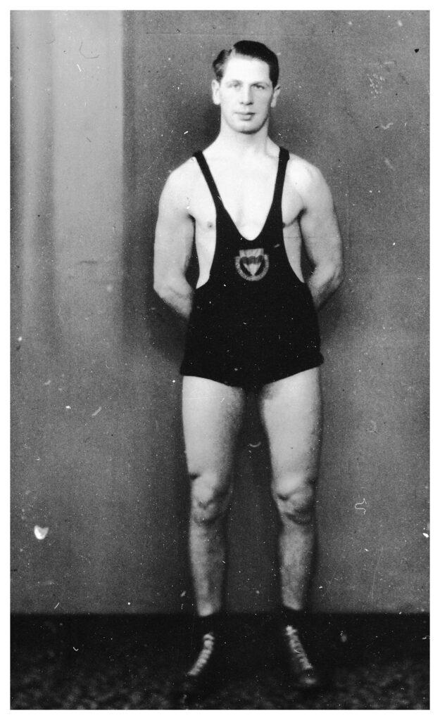 En manlig brottare i brottningdräkt står uppställd för foto.