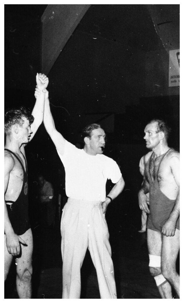 Två manliga brottare på varsin sida om vitklädd domare. Domaren lyfter den ena brottarens hand upp i luften.