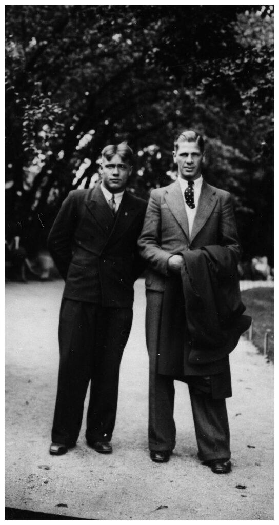 Två stycken kostymklädda män i en park.