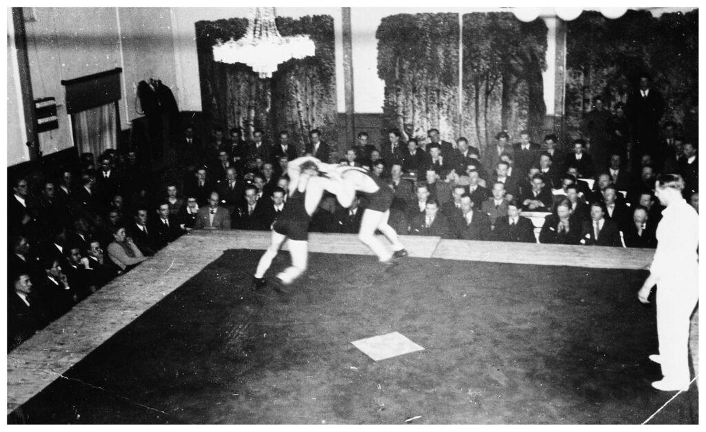 Två manliga brottare brottas på en brottningsmatta. Runt mattan sitter ett femtiotal människor och tittar på. Till höger i bild står en domare och granskar brottningen.