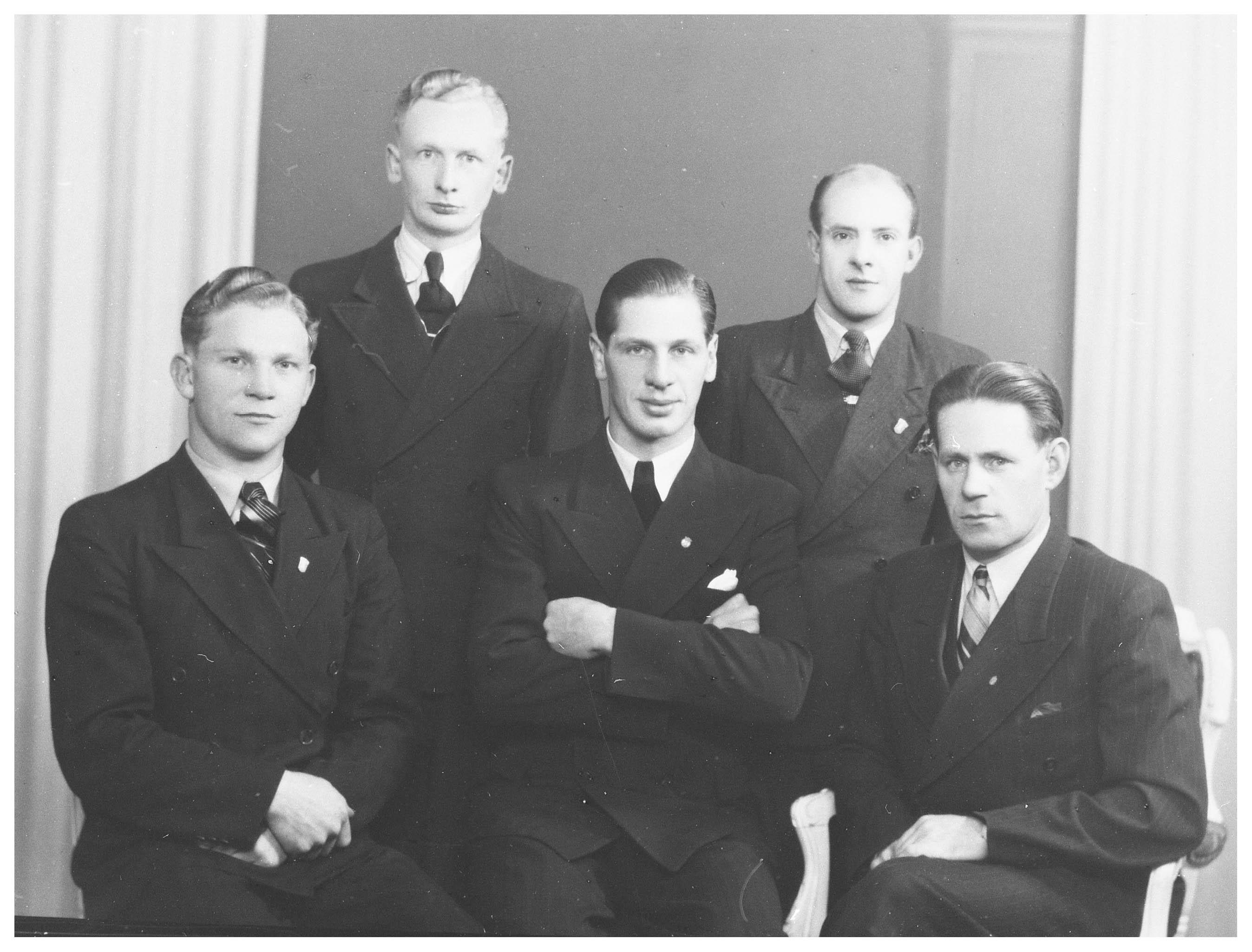 Fem män uppställda för foto. Samtliga bär mörk kostym, skjorta och slips.