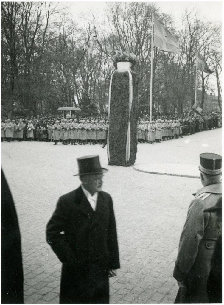 Utomhusfoto. I förgrunden en man i hatt och rock samt ryggen på en militärklädd man. I mitten hög pelare klädd i grönska och blomster. I bakgrunden en stor samling människor.