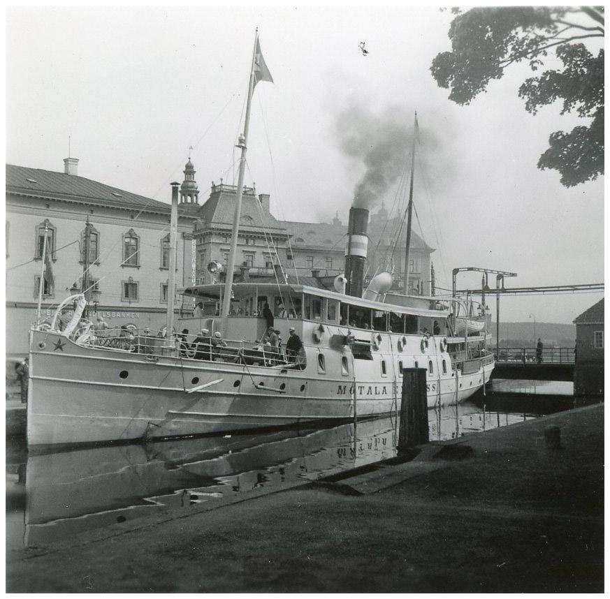 Foto av båt i kanal. I bakgrunden stenhus.