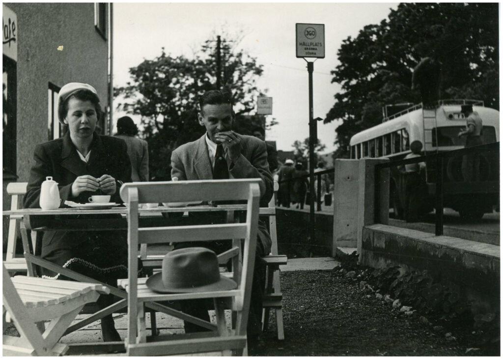 En kvinna och en man sitter vid ett bord och fikar. I bakgrunden en hållplats med en buss.