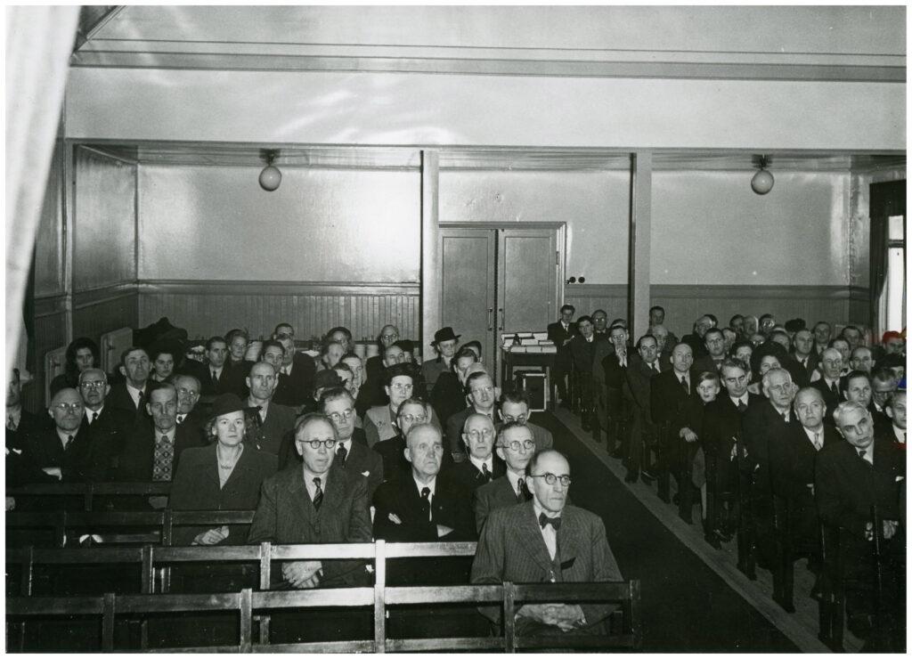 Foto av människor sittandes i bänkar samlade för möte i sal.