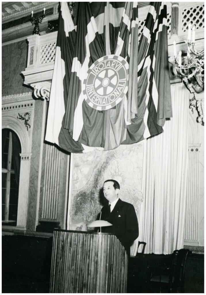 Foto av man vid podium. Ovanför hänger flaggor och vimplar med texten Rotary International.