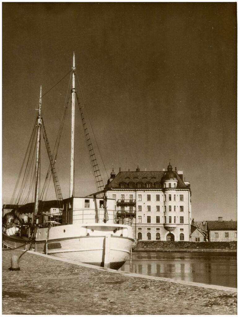 Foto av båt vid kajplats. I bakgrunden stenhus.