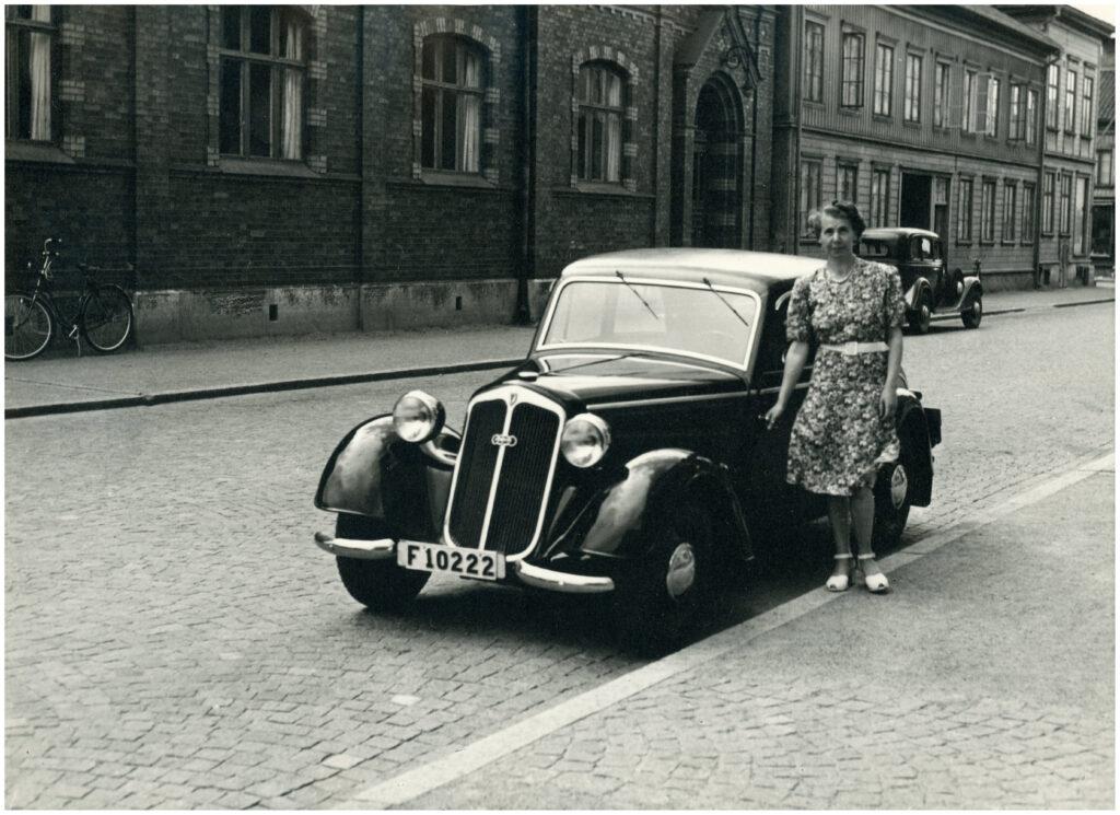 Foto av kvinna i klänning stående vid en bil. Förmodligen 1940- eller 1950-tal. Kullerstensgata. I bakgrunden stenhus.