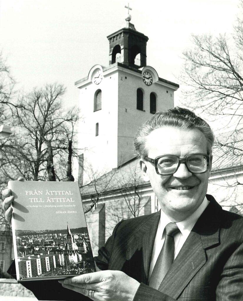 En man håller upp en bok i axelhöjd. I bakgrunden en kyrka.