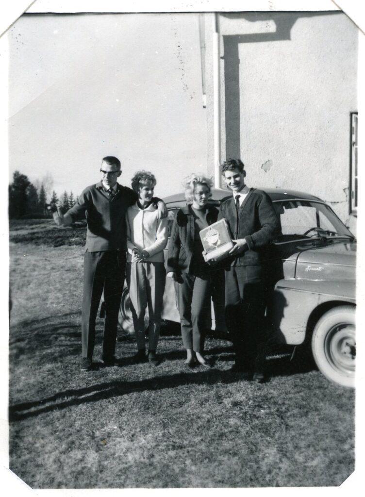 4 personer stående framför en bil.