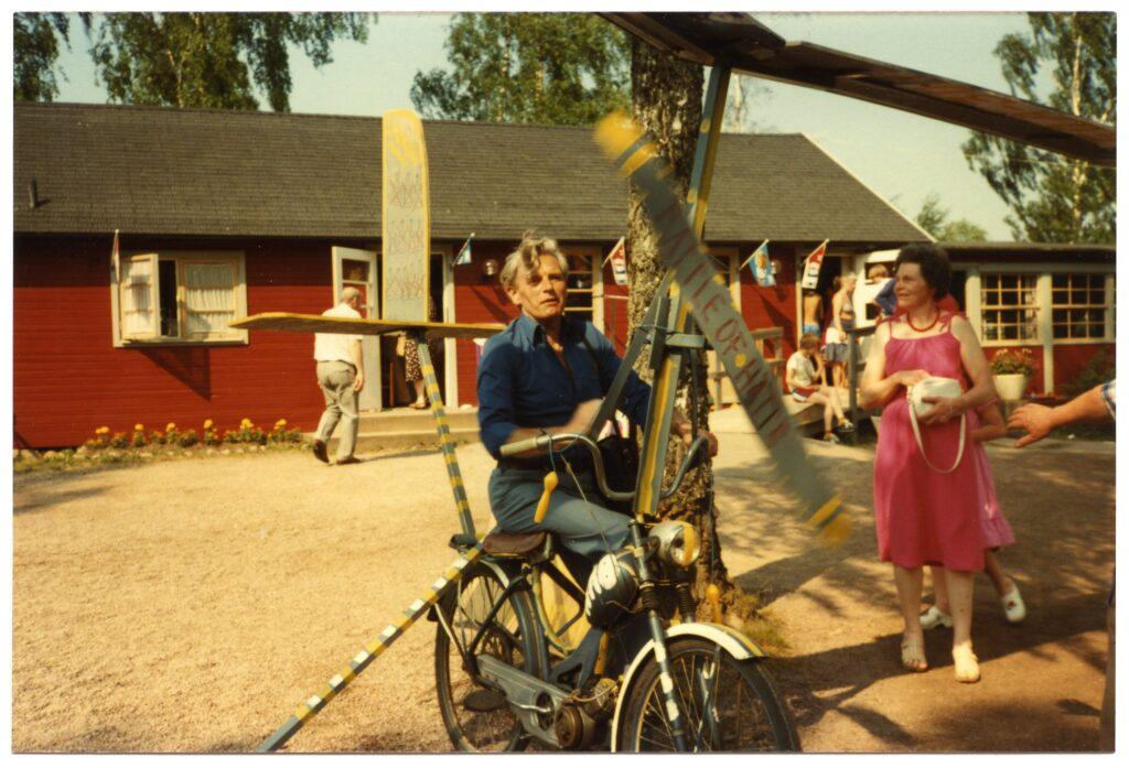 Man på ombyggd moped. Till höger kvinna i rosa klänning. I bakgrunden café i röd stuga.