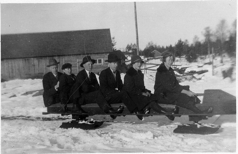 6 stycken ungdomar, två tjejer och fyra killar, sitter på en stor gammaldags kälke. I bakgrunden en lada. Marken är täckt av snö.