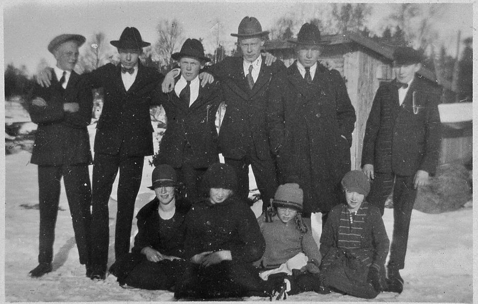 10 ungdomar, både tjejer och killar, uppställda för foto framför en stuga eller ett skjul. Marken är täckt av snö.