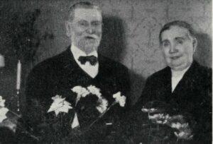 Svartvitt foto på en äldre man och kvinna som håller blomsterkvastar i händerna.