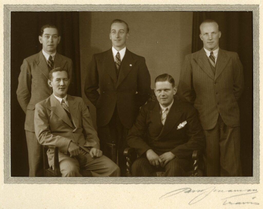 Fem män i kostym uppställda för fotograferingl.